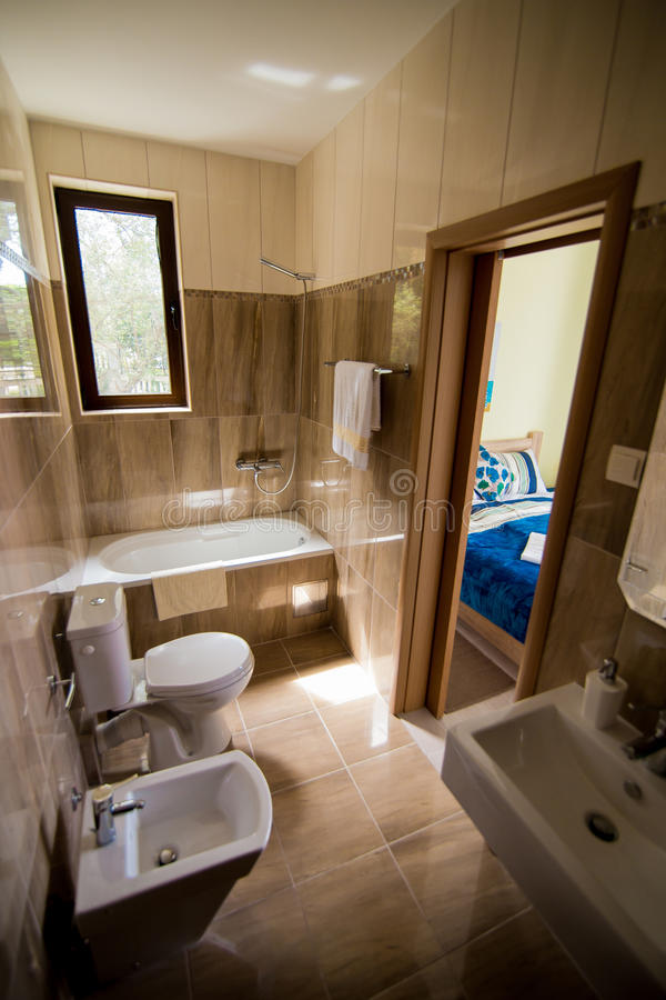 Bathroom interior - washbasin, bidet, toilet, large mirror. The walls are light brown in color. Bathroom interior - washbasin, bidet, toilet large mirror stock photography
