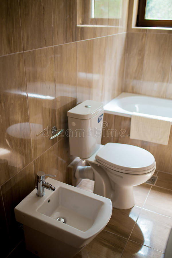 Bathroom interior - washbasin, bidet, toilet, large mirror. The walls are light brown in color. Bathroom interior - washbasin, bidet, toilet large mirror stock image