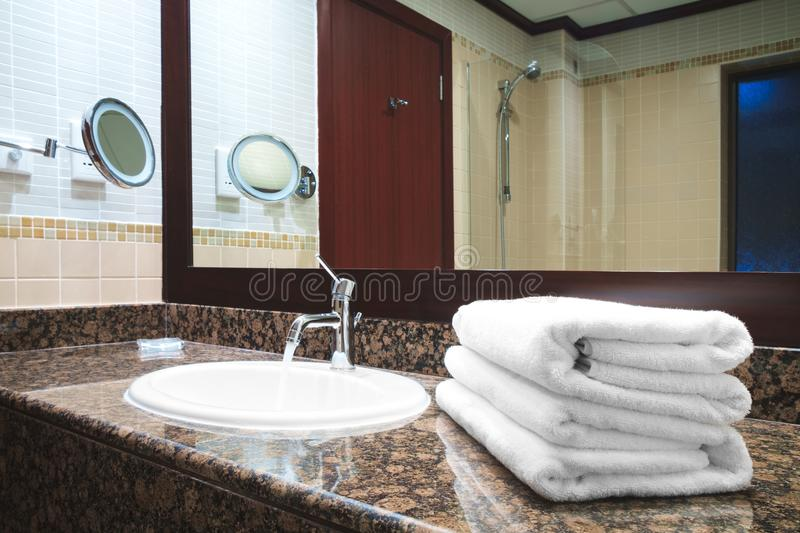 Bathroom luxury classic redwood interior with white sink modern style faucet, white towels drain on stone marble table, water flo. Ws royalty free stock photography