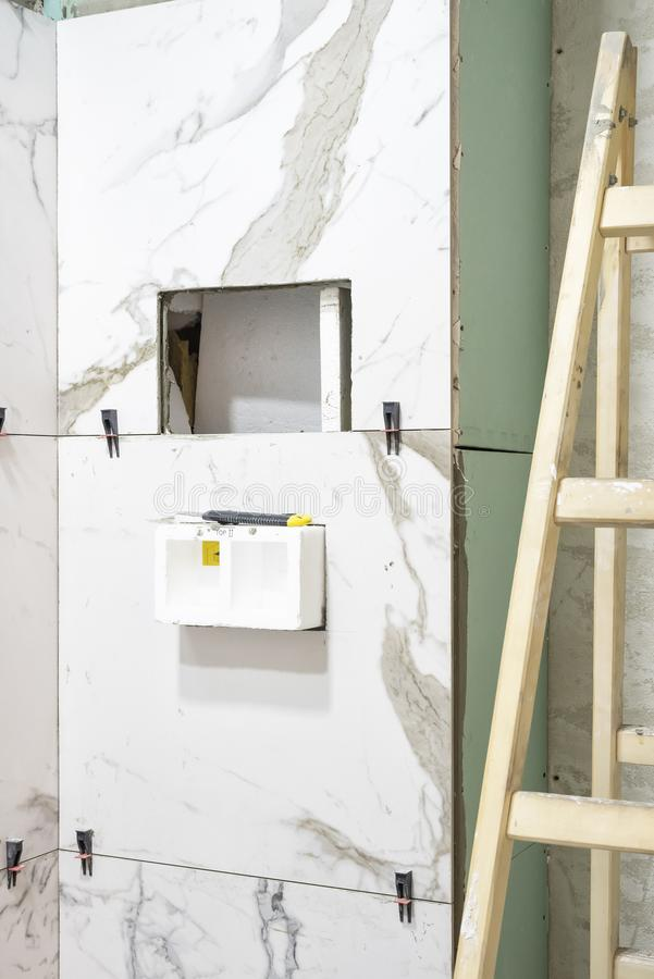 Bathroom renovation concept. Marble ceramic tiles with spacers and grey cement walls in bathroom, renovating and working in toilet stock photography