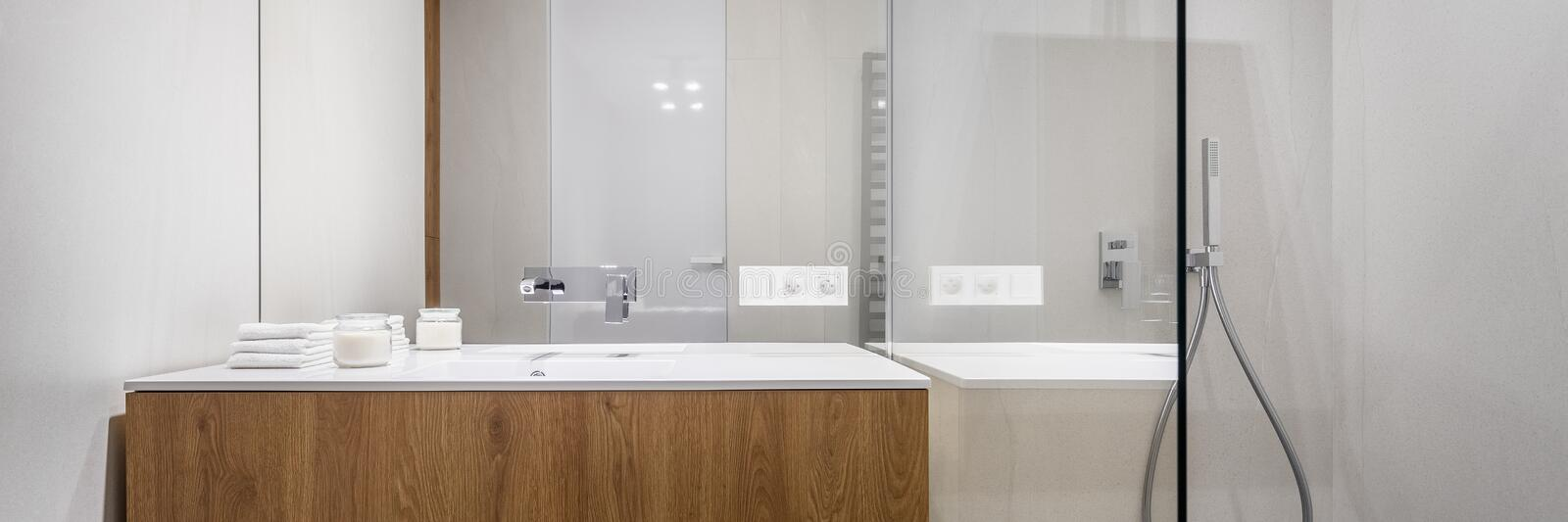 Bathroom with shower, panorama. Panorama of bathroom with shower, big mirror and wooden basin cabinet stock images