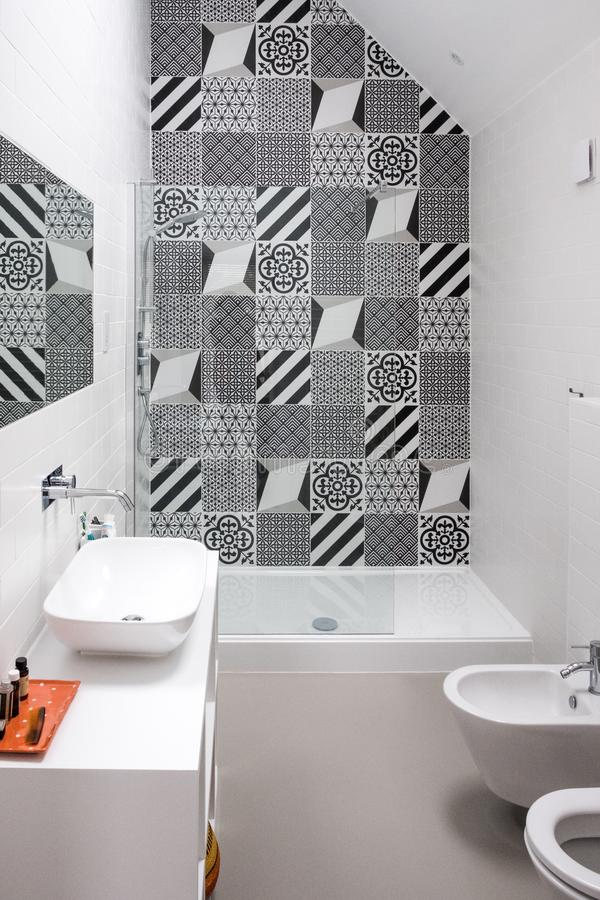 Bathroom with shower unit, toilet, bidet and basin unit, with black and white monochrome patchwork tiles and high ceiling. Bathroom with shower unit, toilet stock images