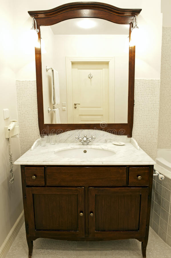 Bathroom sink. Elegant bathroom with the classical marble sink with chrome tap, big mirror and lights stock photography