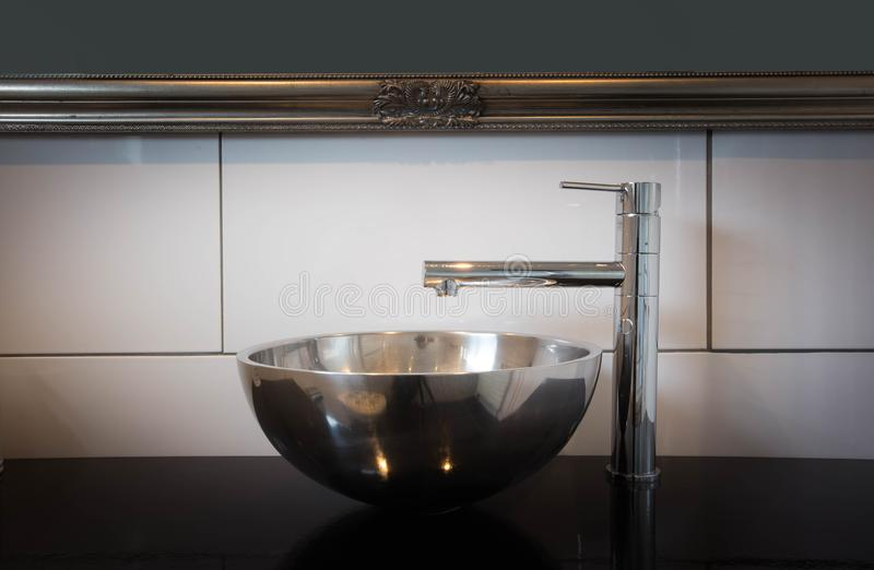 Bathroom sink dark style with silver tap. Bathroom sink dark style modern interior with golden mirror and silver tap royalty free stock images
