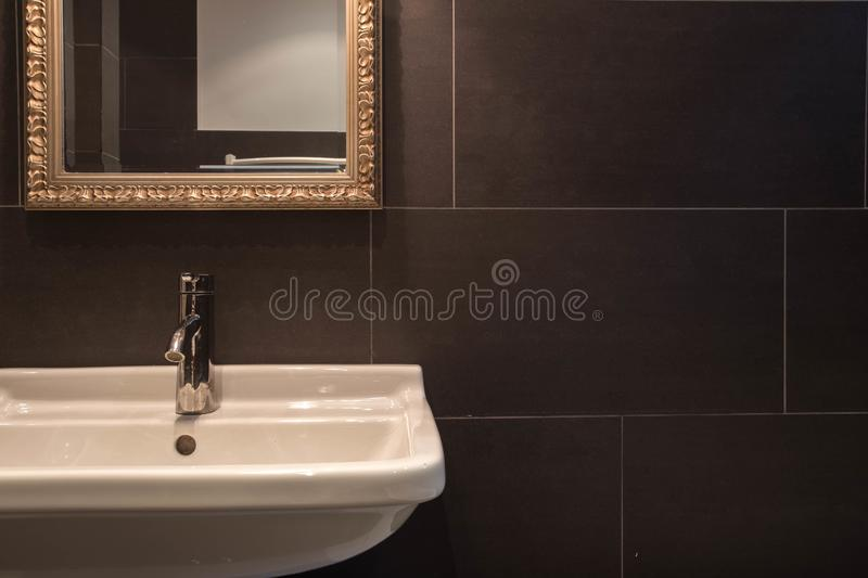 Bathroom sink dark style with silver tap royalty free stock photography