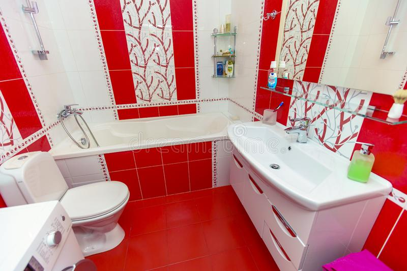 Bathroom in a small apartment. tile with red and white pattern. Toilet, bathroom, sink, mirror stock image
