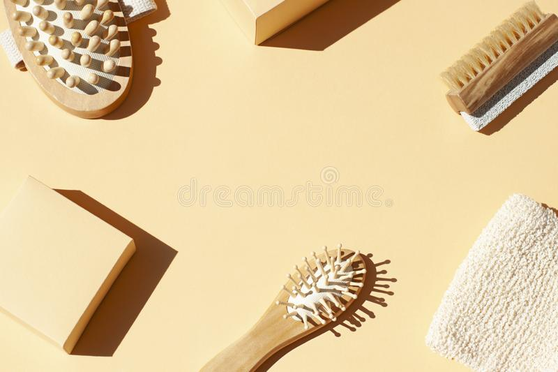 Bathroom, spa accessories concept flat lay on the beige background. Top view frame. With hairbrush , nailbrush with pumice stone, bath mitt and massaging brush stock images