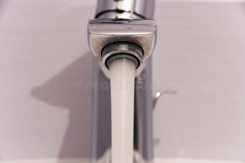 Bathroom tab. A modern basin mixer tap in a contemporary bathroom stock image