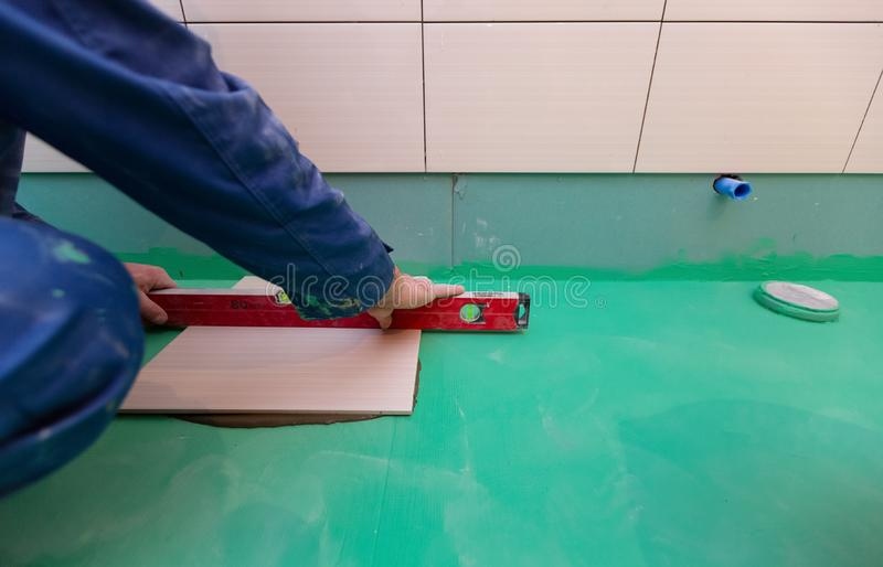 Bathroom tiles replacing. Caucasian worker is installing brand new ceramic tiles in bath is inder construction. Remodeling, renovation, overhaul, extension stock images