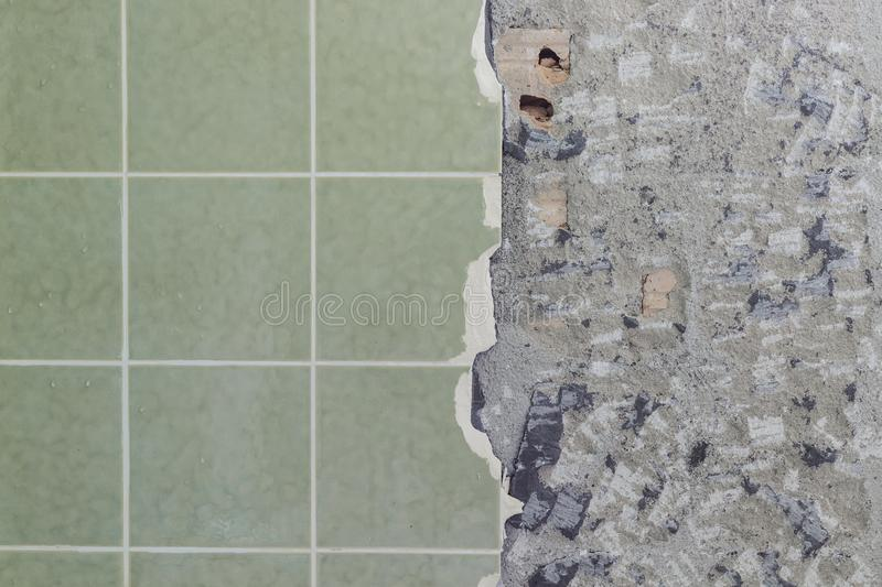 Bathroom tiles wall besides cracked and destroyed undersurface royalty free stock image