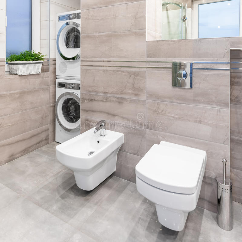 Bathroom with toilet and bidet. Beige bathroom with mirror, toilet, bidet, washer and clothes dryer royalty free stock photo