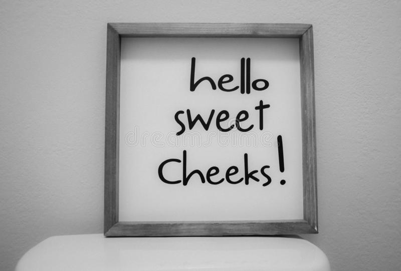 Sign on toilet `hello sweet cheeks` royalty free stock photography