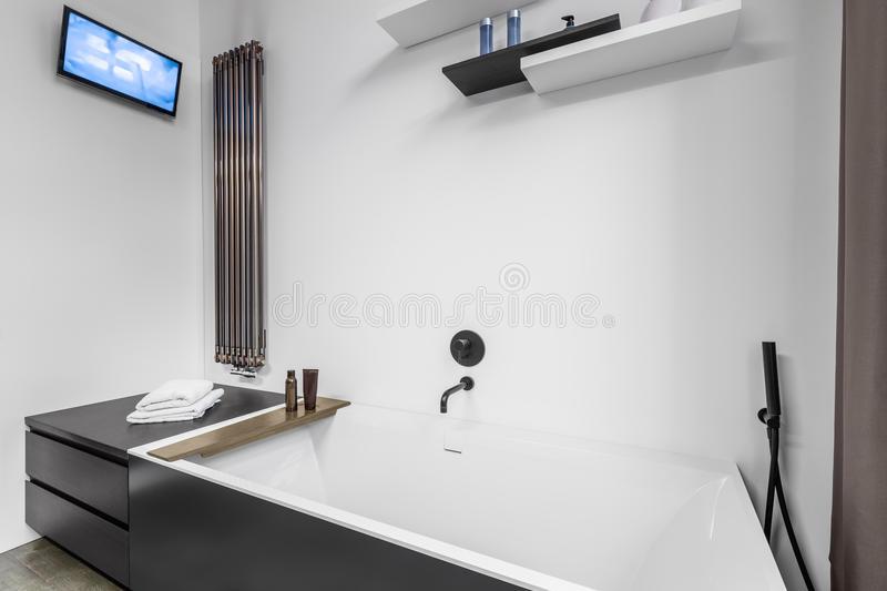 Bathroom with tv and bathtub. Fancy bathroom interior with small tv and modern bathtub royalty free stock photo