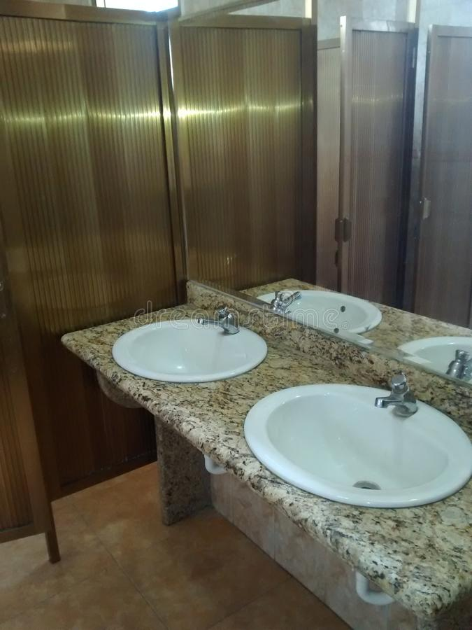 BATHROOM WITH TWO LAVAMENTS IN GRANITE. BATHROOM WITH TWO LAVAMANOS IN GRANITE WITH DIVISION IN ALUMINUM COLOR GOLD TWO LAVAMANOS WHITE IN LUXURIOUS FINISH WITH stock images