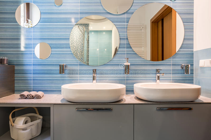 Bathroom with two sinks. Blue bathroom with two sinks and oval mirrors stock photos