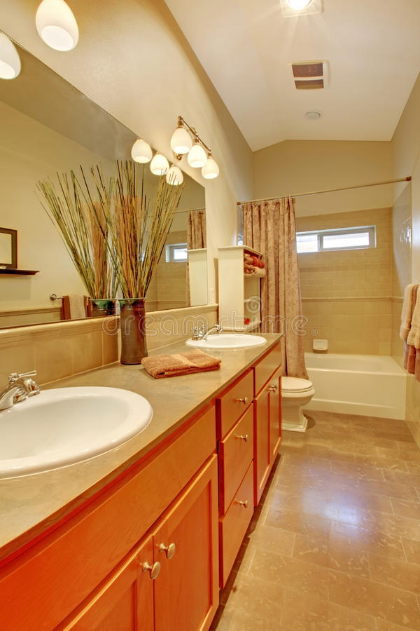 Bathroom with two white sinks and maple cabinets stock photography