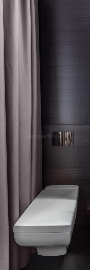Bathroom with wall mounted toilet. Dark bathroom with white wall mounted toilet, vertical panorama stock photo