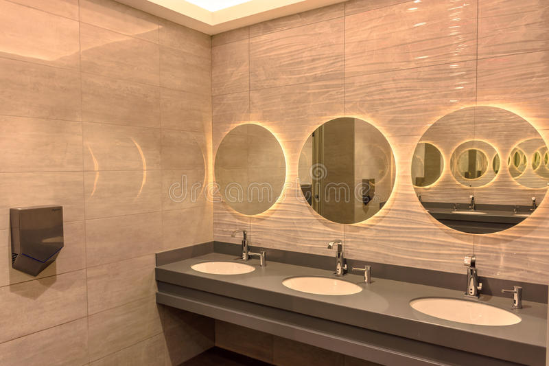 A bathroom with a washbasin and mirrors.  royalty free stock photo