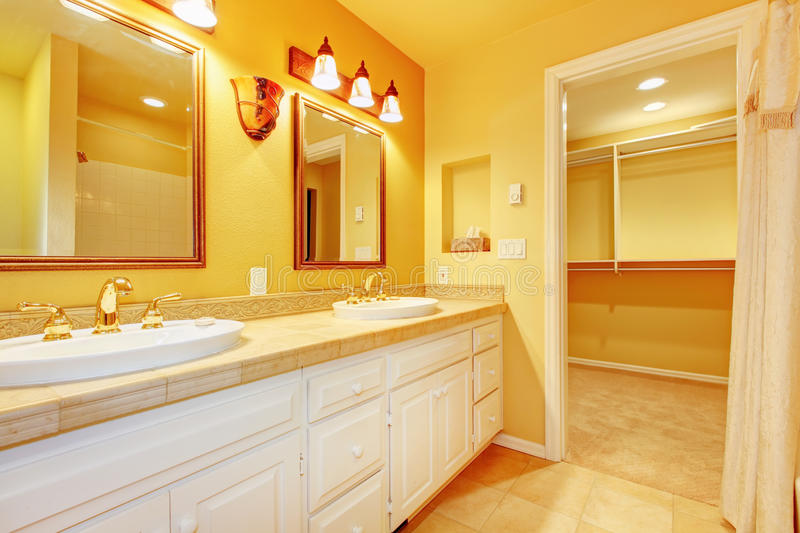 Bathroom with white cabinets and gold walls stock photo for White stock cabinets