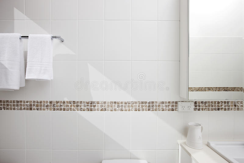Bathroom White Tiles Background. Detail of a bathroom showing the tiling, mirror and bath towels with a shaft of sunlight running through