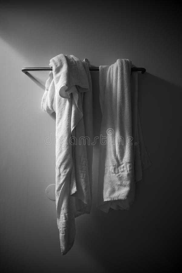 Bathroom. White towels in a colgador with lateral lighting stock photography
