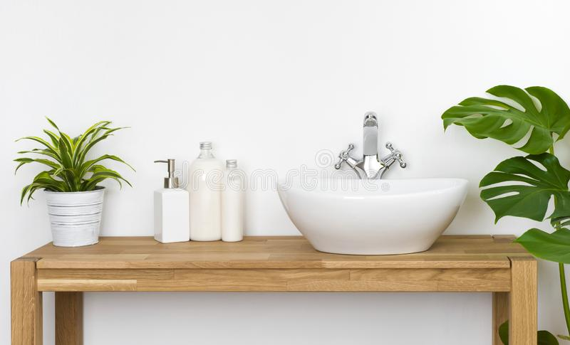 Bathroom wooden table with washbasin, faucet, plants and soap bottles stock photography