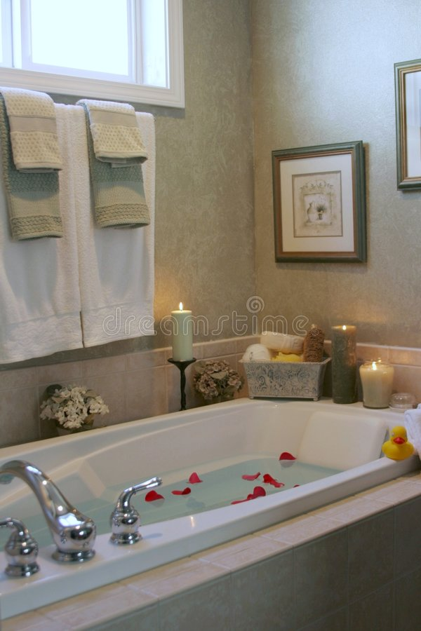 Bathtime. Bathwater and rose petals make this bathroom very inviting stock image