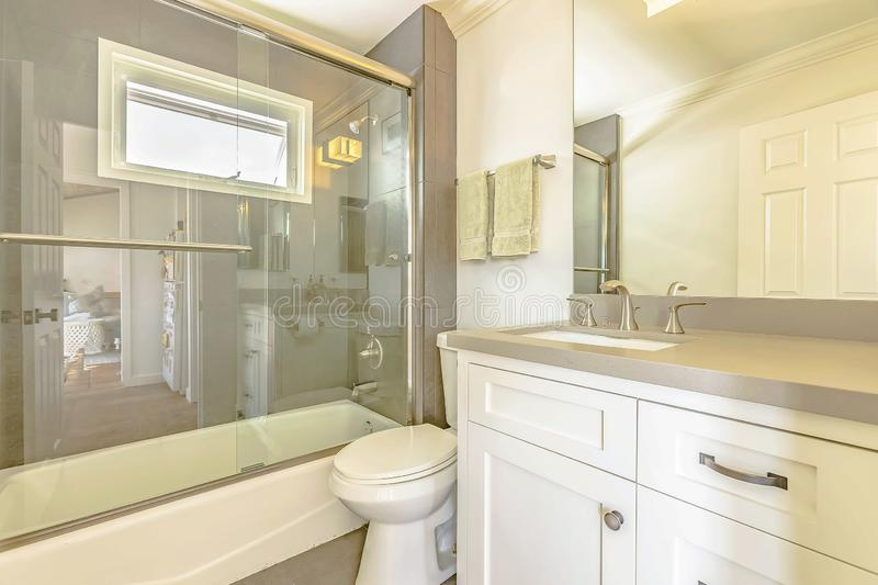 Bathtub and shower with glass door and window inside the bathroom of a home. The toilet and vanity unit can also be seen in this small room stock images
