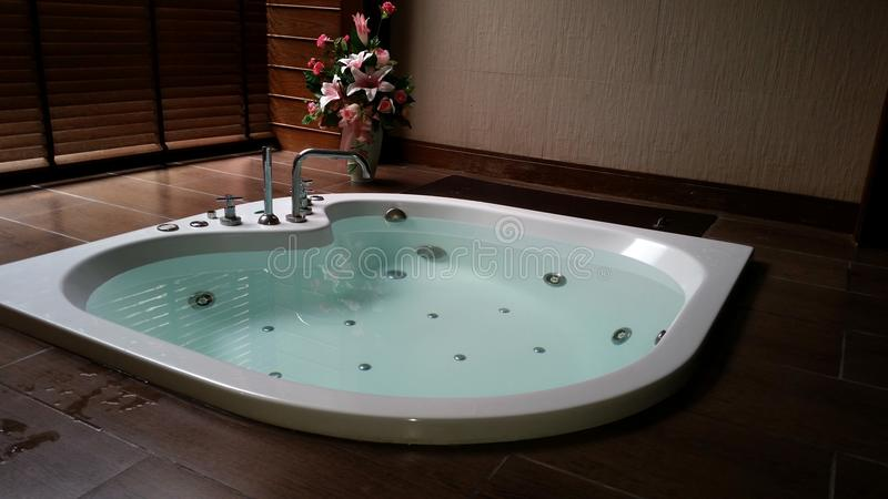 Bathtub on the tile floor with water on bathroom royalty free stock photography