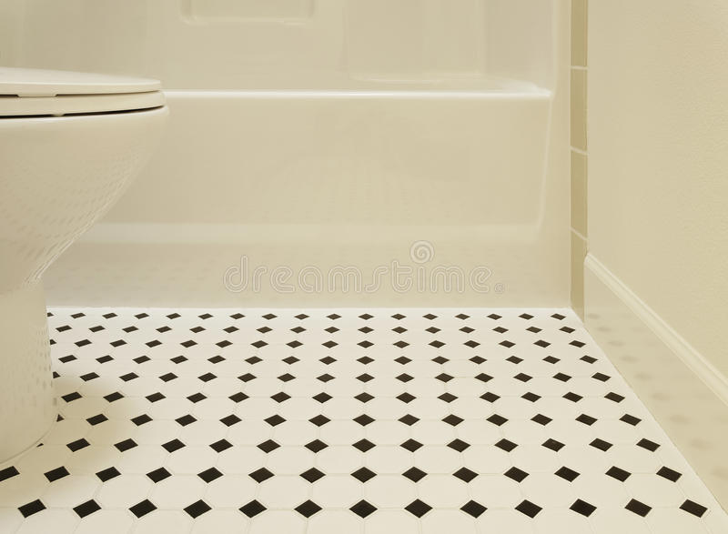 Bathtub And Toilet. A white acrylic bathtub and porcelain toilet of a bathroom are sitting on a diamond patterned vinyl flooring in a bathroom. Horizontal shot stock images