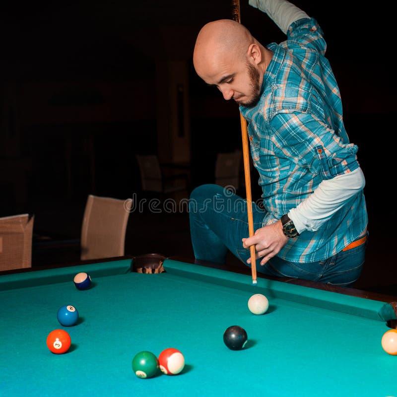 A batida difícil está preparando-se para executar um jogador na mesa de bilhar fotografia de stock royalty free