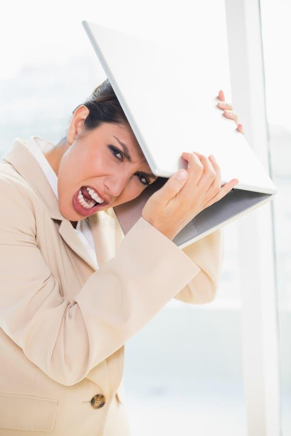 A batida enlouquecida da mulher de negócios dirige fora o portátil que olha a câmera imagem de stock
