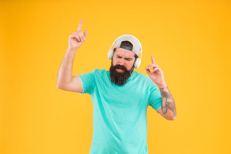 Batida nova do partido de disco Homem do DJ no fundo amarelo Indivíduo não barbeado que aprecia o acordo que joga no partido do D fotos de stock royalty free