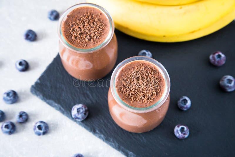 Batido da banana do chocolate com sementes e mirtilo do chia no precários imagens de stock royalty free