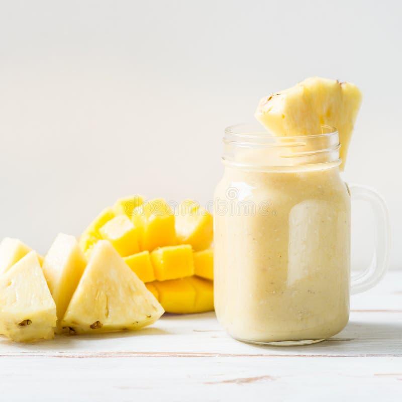 Batido da manga, da banana, do abacaxi e da farinha de aveia no frasco imagens de stock royalty free
