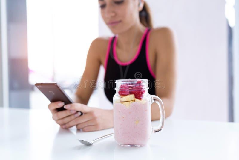 Batido da morango e da banana No fundo, jovem mulher desportiva que usa seu telefone celular imagem de stock