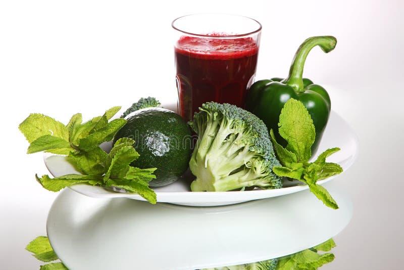 Batido das beterrabas no vidro, perto dos brócolis frescos, pimenta verde, abacate foto de stock