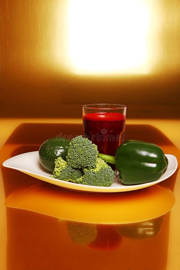 Batido das beterrabas no vidro, perto dos brócolis frescos, pimenta verde, abacate imagem de stock royalty free