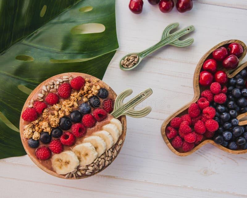 Batido de Acai, granola, sementes, frutos frescos em uma bacia de madeira com colher do cacto Placa enchida com as bagas no branc imagens de stock
