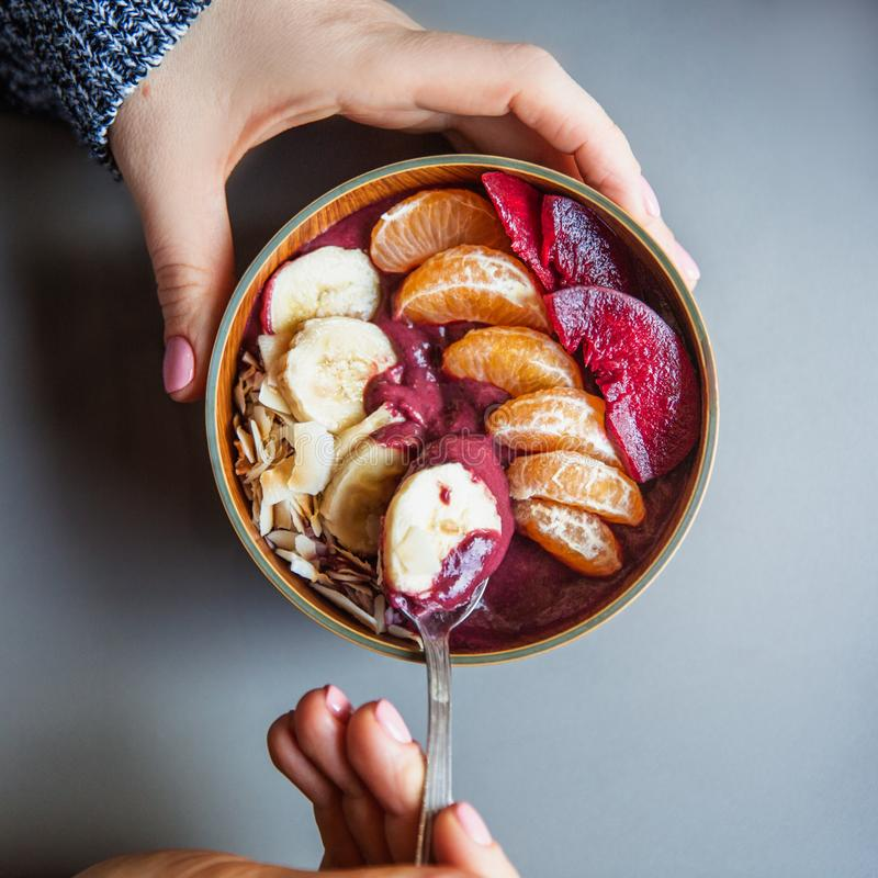 Batido de Acai, granola, sementes, frutos frescos em uma bacia de madeira nas mãos fêmeas na tabela cinzenta Comendo a bacia saud imagens de stock