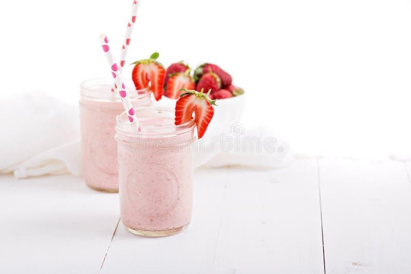 Batido de leche de la fresa en tarros de albañil imagen de archivo