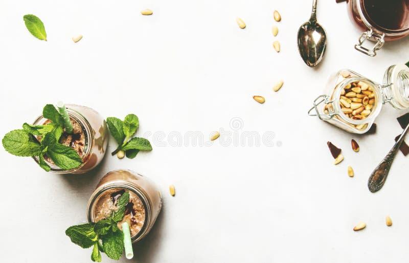 Batido de leche del chocolate o cóctel de la leche con el desmoche, la menta verde y las nueces de cedro, tabla de cocina blanca, imagen de archivo libre de regalías