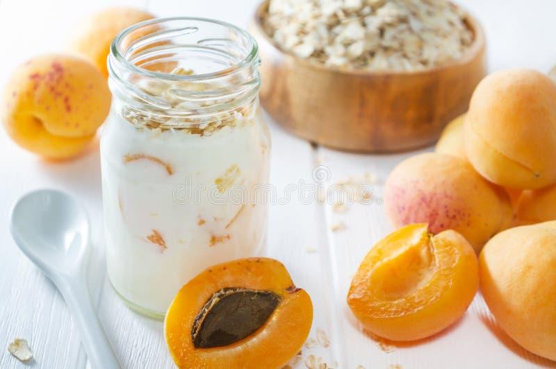 Batido de leche, smoothie o yogur de la harina de avena con el albaricoque fresco en una tabla de madera blanca fotos de archivo