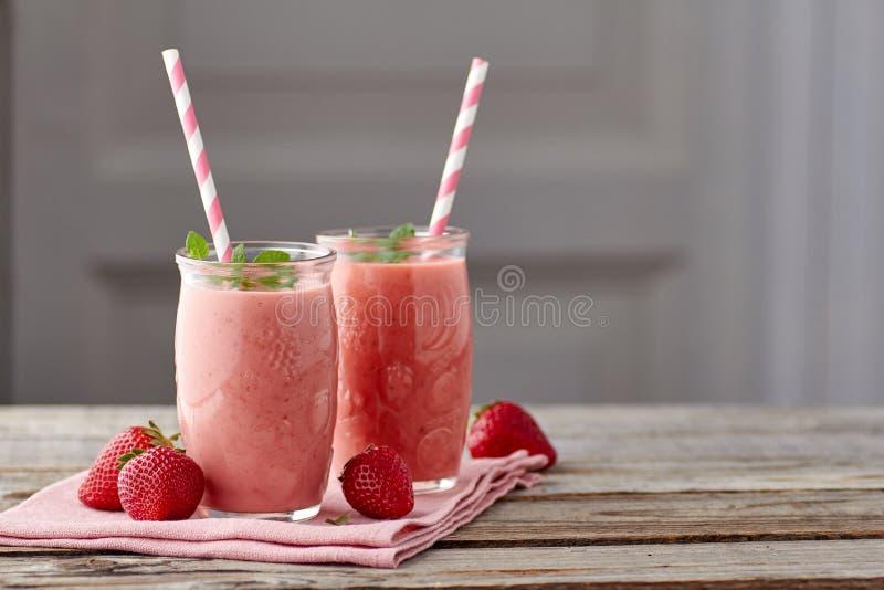 Batido do iogurte e da morango em dois frascos com palha bebendo na tabela de madeira fotos de stock