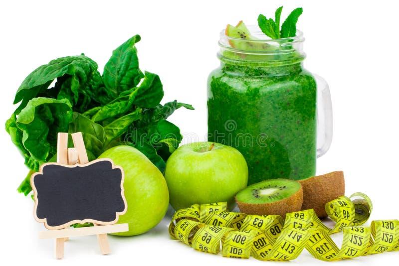Batido e ingredientes verdes saudáveis no branco - espinafre, maçã imagens de stock royalty free