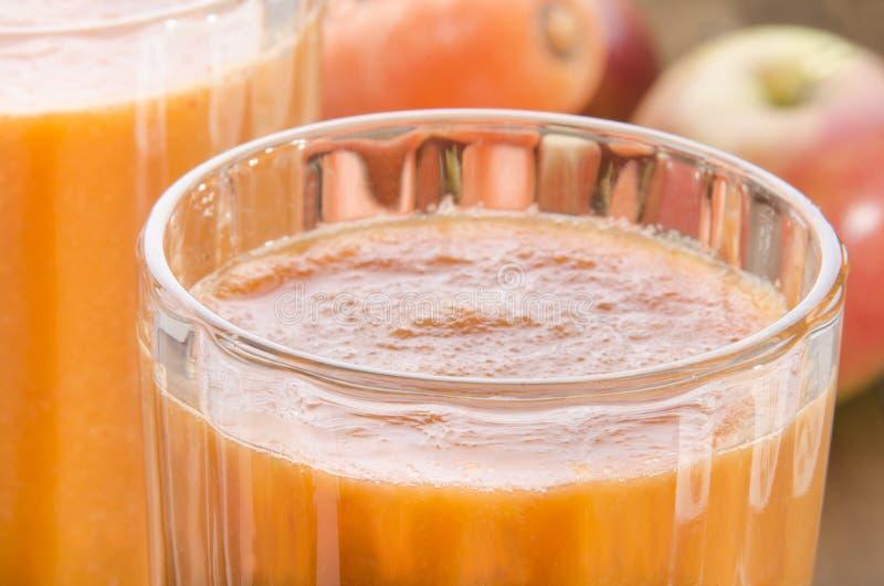 Batido fresco da cenoura e da maçã em um vidro fotos de stock royalty free