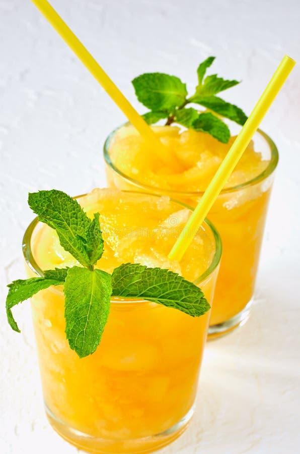 Batido frio do melão do verão com as folhas de hortelã fresca no fundo branco Suco do melão em dois vidros Cocktail da desintoxic imagem de stock royalty free