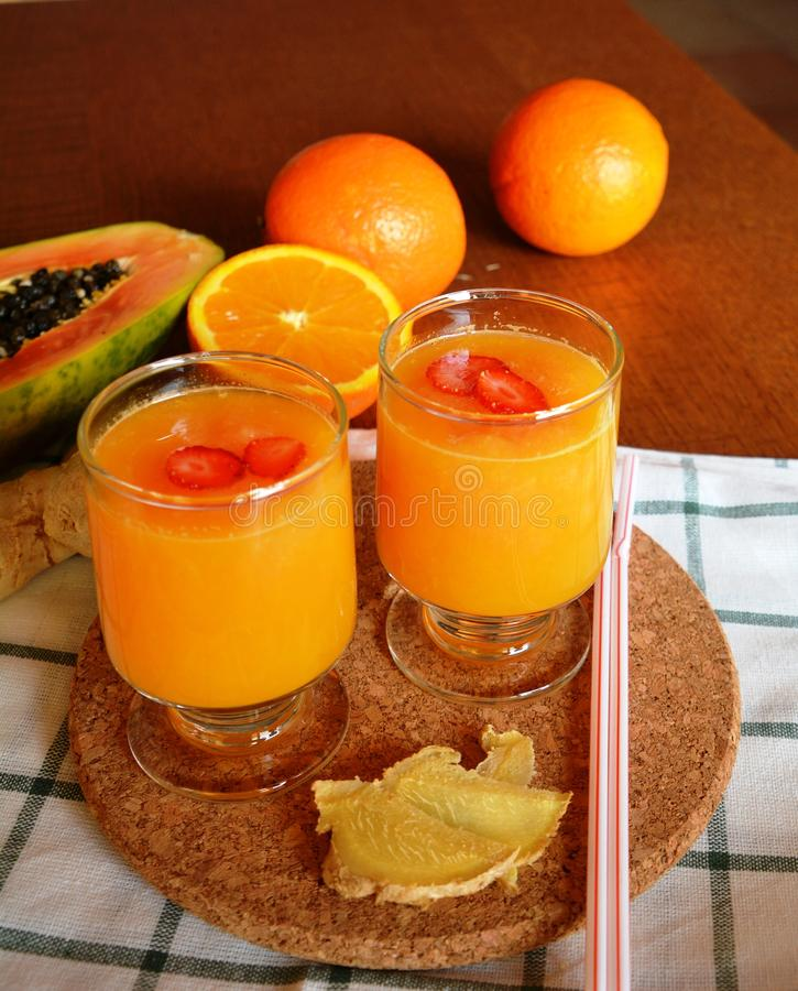 Batido saudável da laranja, da papaia e do gengibre em uma tabela de madeira foto de stock royalty free