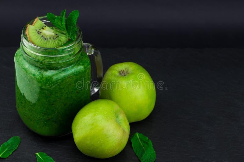 Batido verde com frutas e legumes no fundo preto W imagens de stock