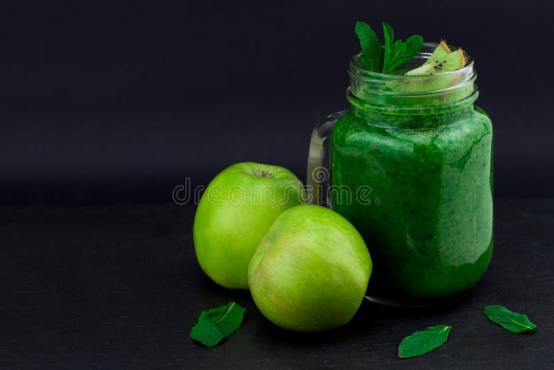 Batido verde com frutas e legumes no fundo preto W foto de stock